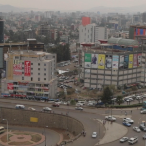 A shot of the skyline of the city of Addis Ababa, Ethiopia, with traffic moving around a traffic circle in the foreground.
