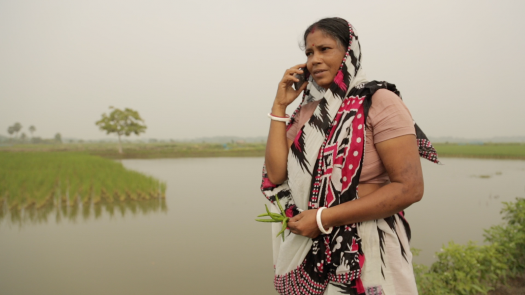 A Bangladeshi woman farmer wearing a pink, black and white sari and light pink shirt stands next to an aquaculture pond and holds a cell phone up to her ear. In her other hand, she holds green freshly picked chilis.