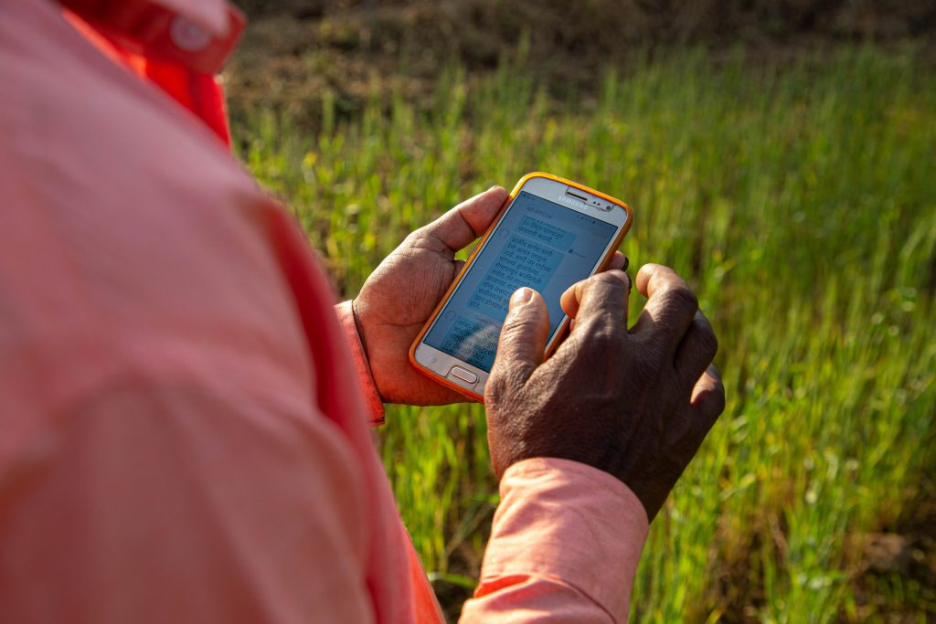 The camera looks over the shoulder of a person in a pink collared long-sleeve shirt as they scroll through text messages on a white smart phone in an orange plastic case. In the background is a field of wheat.