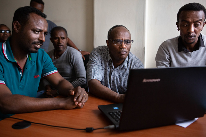 Tufa Dinku, the country lead for ACToday Ethiopia, demonstrates the maprooms with a team from the National Meteorological Agency. Dr. Dinku squints at a laptop whose screen faces away from the camera and his hand hovers over the scrollpad. On either side of him are members of the Ethiopian National Meteorological Agency who look on with interest at the screen.