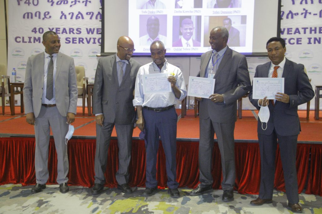 Tufa Dinku (middle) holds the document identifying IRI as a key partner in the development of Ethiopia's National Framework for Climate Services, alongside several government officials on June 8, 2021. Five men stand in front of a red curtained stage that is set up for a panel with slides projected on a white screen. Three of the men hold white certificates, including Tufa Dinku, in the center.