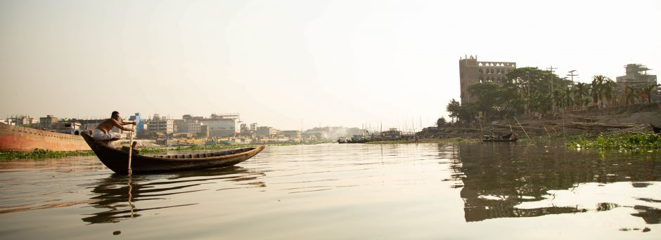 A Bangladesh man punts an empty boat across a river, with buildings of Dhaka in the background.