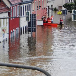 A flooded street in Germany with a rescue boat pulled up to a window to evacuate people from a building.